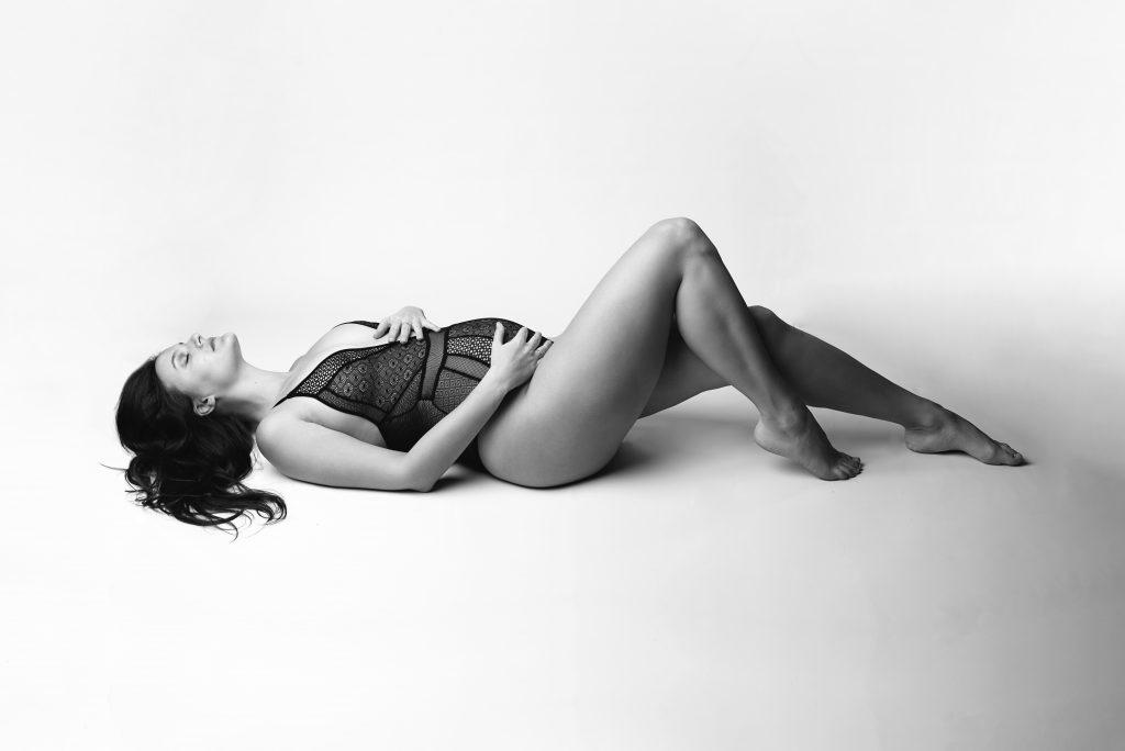 Photo en noir et blanc tirée d'une séance photo grossesse en studio. Une future maman est allongée en body de grossesse sur un fond blanc.